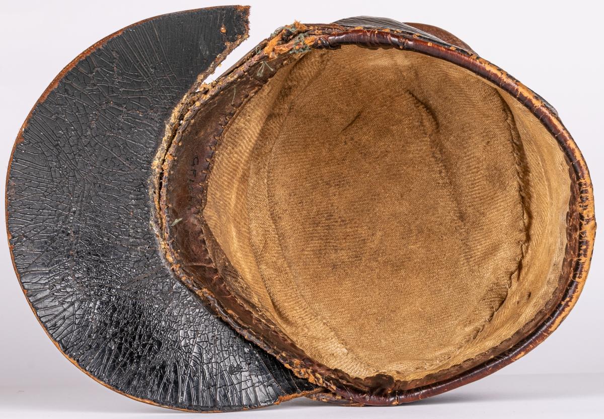 Mössa av läder, skinnkaskett, brun, med bred svart skärm av papp. Låg uppvikt kant nertill, sammanfästad framtill med sölja. Kullen sydd i tre delar. Innermått 15*20cm.
