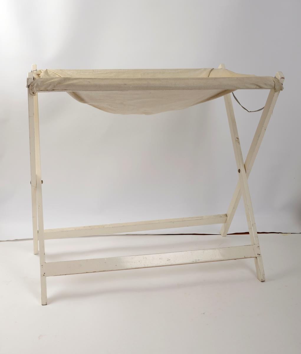 Hvitt stellebord i tre, gummiert stoff med tilhørende badekar til baby.