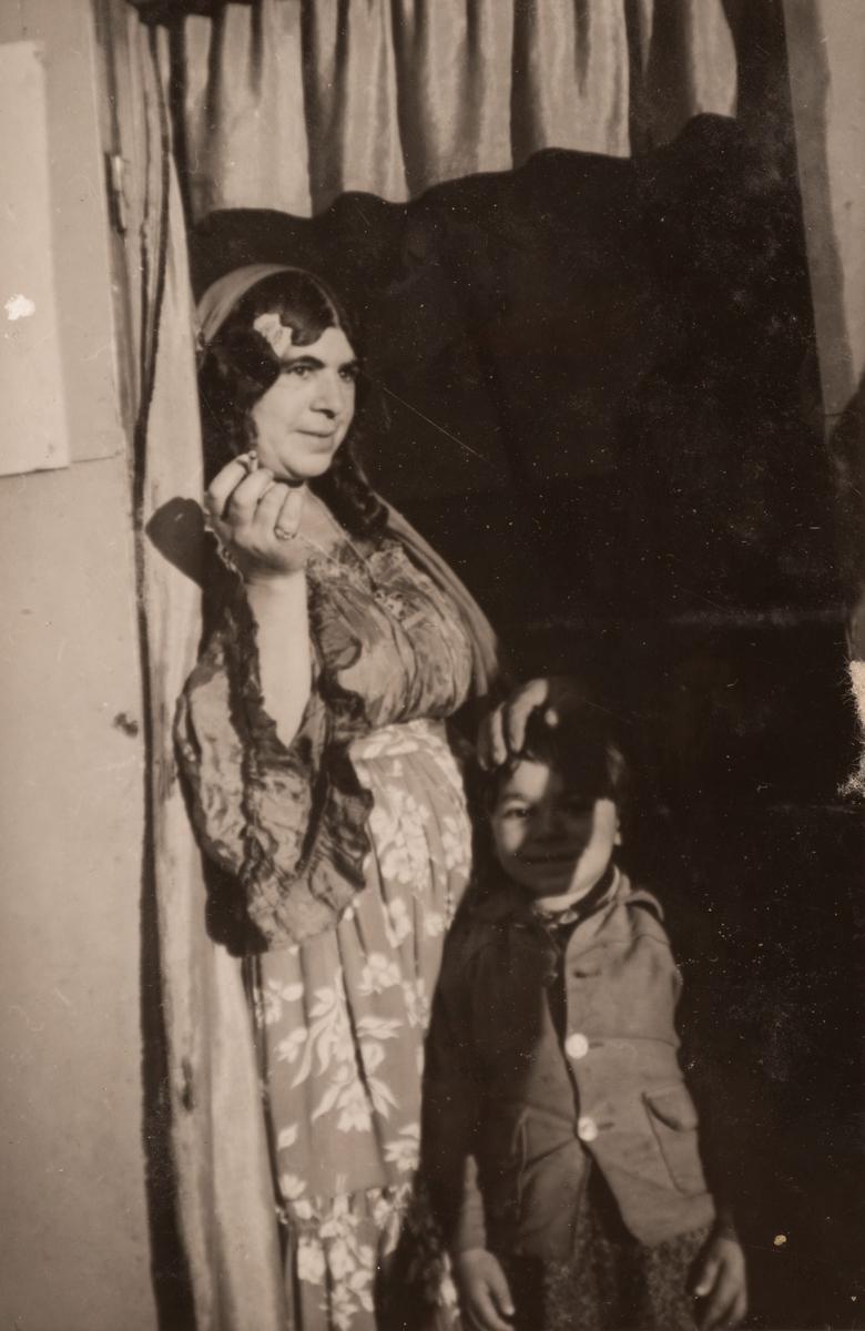 En romsk kvinna står i dörröppningen till en bostadsvagnmed en liten pojke framför sig. Fotografiet är taget september 1947 i Backa, en liten by strax utanför Jäderfors, omkring 7km norr om Sandviken.