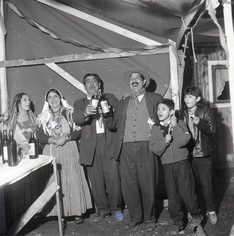 Bröllopsfestligheter i november 1958 i Nyköping. Fotografiet är taget i ett av tälten med några av släktingarna till brudparet. Svenska romer har historiskt tvingats bo i läger, ofta i samhällets utkant, då man har förvägrats fast bostad och fördrivits. Toleransen för romer har historiskt varierat mycket mellan olika samhällen, men romers närvaro har sällan setts som något positivt. Efter att de svenska romerna i Sverige erkändes som medborgare år 1952 uppstod debatt kring gruppens svåra levnadsförhållanden. En statlig utredning genomfördes under 1954-1956 där en av slutsatserna blev att fast bostad var nyckeln till att lyckas med skolgång och arbetsliv. Från och med mars 1960 hade möjlighet att rekvirera statsbidrag för kostnader i samband med romers bosättning, vilket förenklade möjligheten för svenska romer att få tillgång till permantenta bostäder samt i förlängningen studier och arbete.