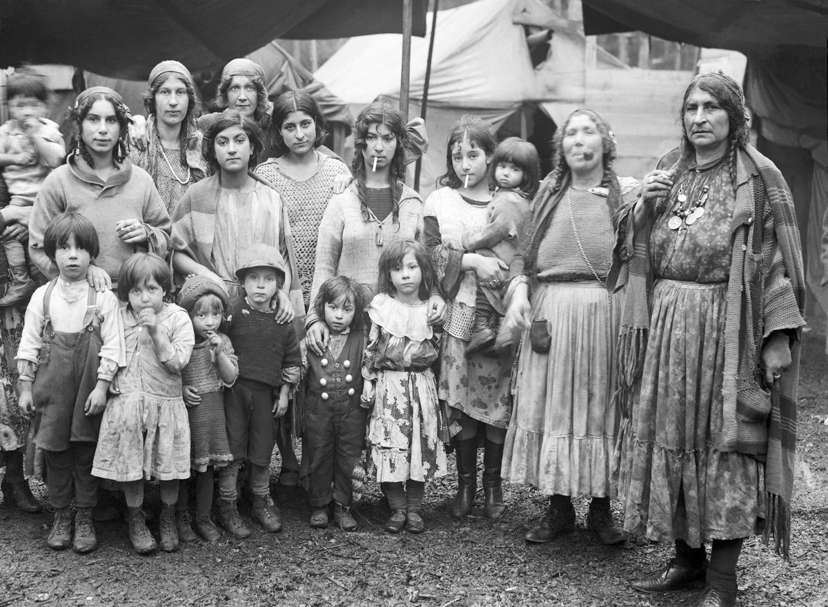 En grupp romska kvinnor och barn uppställda för fotografering. I bakgrunden syns tält. Boendestandarden bland svenska romer var under 1900-talets första hälft mycket varierande. Familjer som hade det bättre ställt kunde äga flera tält, medan fattigare familjer enbart hade ett tält. Man sov då där marken var minst lerig. Under 1940-talet förbättrades levnadsstandarden och flera svensk-romska familjer specialbeställde nu bostadsvagnar. Att inte behöva sova på marken utgjorde en avsevärd förbättring av livskvaliteten. Eftersom vagnarna specialbeställdes kunde beställaren vara med och påverka vagnens utformning. Ofta fanns sovgemaket längst in, varpå vardagsrummet följde och köket låg längst ut. Denna utformning kunde dock skilja sig åt mellan olika vagnar. Generellt var dock vagnarna dåligt isolerade och kalla att bo i. Först på 1960-talet tilläts svenska romer att bli bofasta.