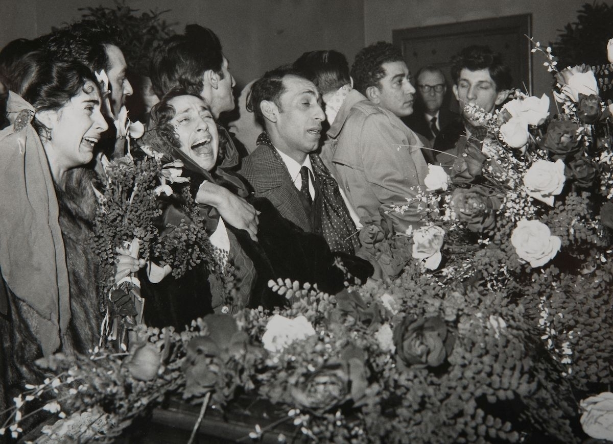 Bilden är tagen vid en romsk begravning i Stockholm år 1959. Författaren och människorättskativisten Katarina Taikon beskriver i en av sina böcker hur sederna kring begravningar såg ut bland romer medan man fortfarande bodde i läger. Taikon berättar att det inom den romska kulturen inte anses vara någon skam att gråta och visa känslor, utan sorgen uttrycks i högljudd klagan. När någon dog i ett läger fick ingen av de närmast sörjande arbeta, laga mat eller tvätta kläder. Man fick inte sova på tre dagar, utan skulle vara vaken och tala om den döde. Därpå följde begravningen. Före jordfästningen lyftes kistlocket av för att låta släktingar säga ett sista farväl.