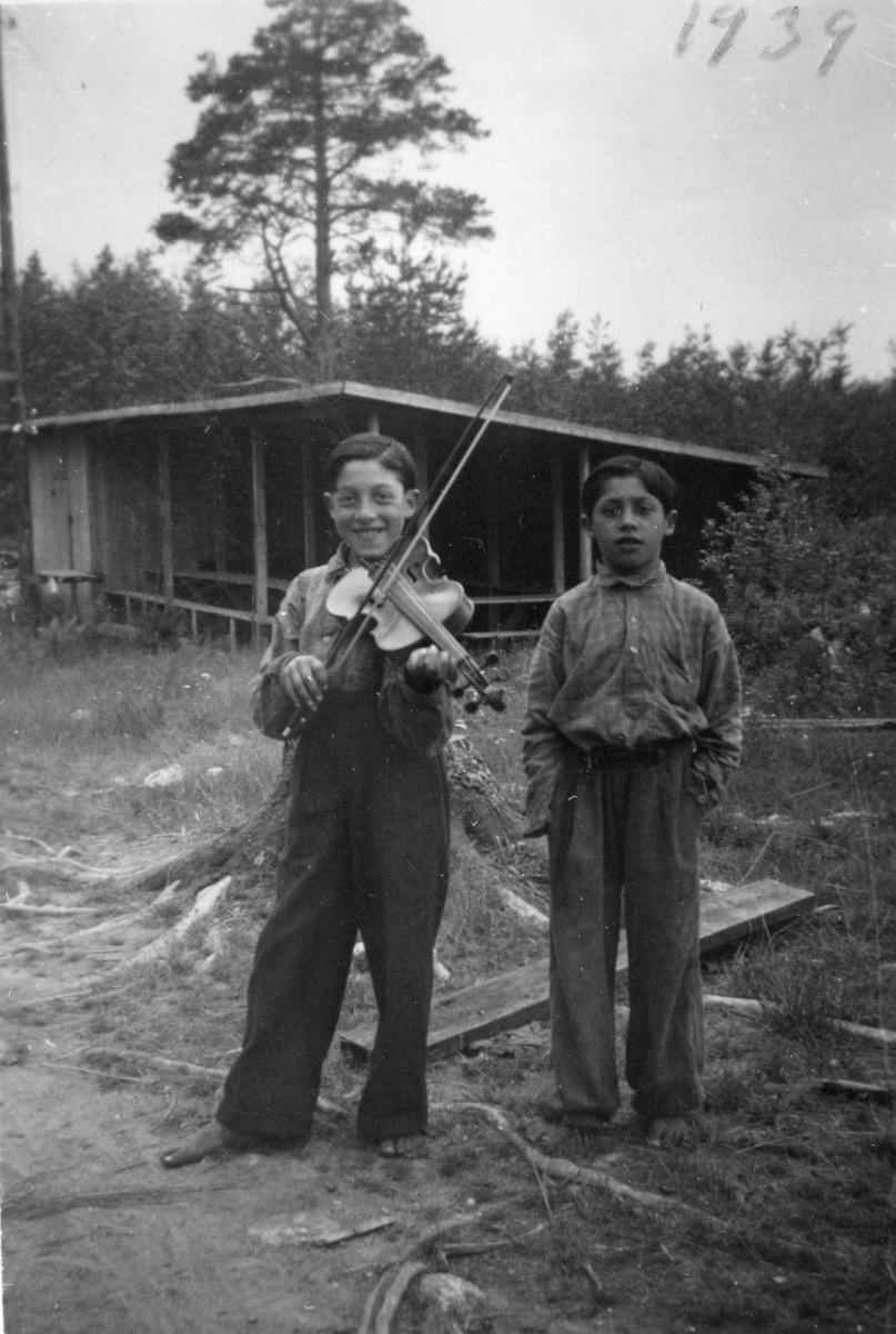 """Strax utanför Enånger, invid vad som då kallades för """"Lars-Isaksbacken"""", fanns under 1900-talets första hälft en plats där romska grupper fick slå läger. Bilden är tagen år 1939 vid den dansbana som då fanns på platsen. Det är tyvärr inte känt vilka personerna på bilderna är. Fram till 1960-talet levde de flesta romer i Sverige som kringresande och saknade fast bostad. Man bodde i tält eller vagnar, tvungna att flytta från plats till plats. Lägerplatser fanns ofta nära dansbanor, då arbete inom musik och underhållning varit vanligt bland romer och resande. Att musicera kunde vara ett sätt att tradera berättelser och traditioner såväl som ett sätt att tjäna sitt levebröd. Samtidigt kunde det vara ett sätt att få uppskattning från lokalbefolkningen, vilket kunde resultera i möjligheten att få stanna längre på samma plats. Romer och resande har historiskt utsatts för hård diskriminering. År 1885 stiftades en lag i Sverige som gjorde det olagligt att vara arbetslös, egendomslös eller kringvandrande. Samtidigt började kommunerna under 1900-talets första årtionden att utfärda vistelseförbud, lägerslagningsförbud och näringsförbud för romer och resande. Tältliknande hus var lätta att montera ned när ordningsmakten eller lokala bråkmakare bestämt sig för att fördriva de boende."""