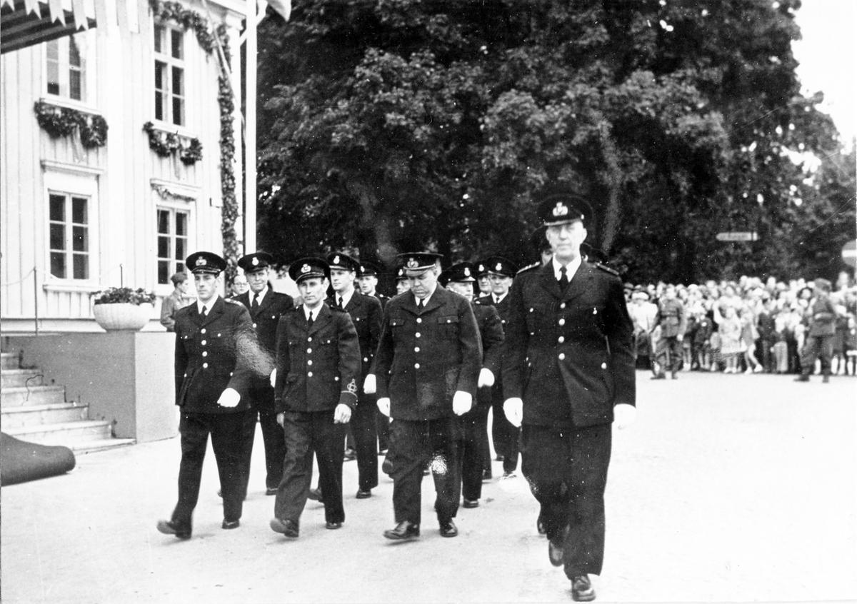 Brandkårens 50-årsjubileum. En grupp män i uniform går förbi Rådhuset medan en folksamling tittar på uppvisningen.