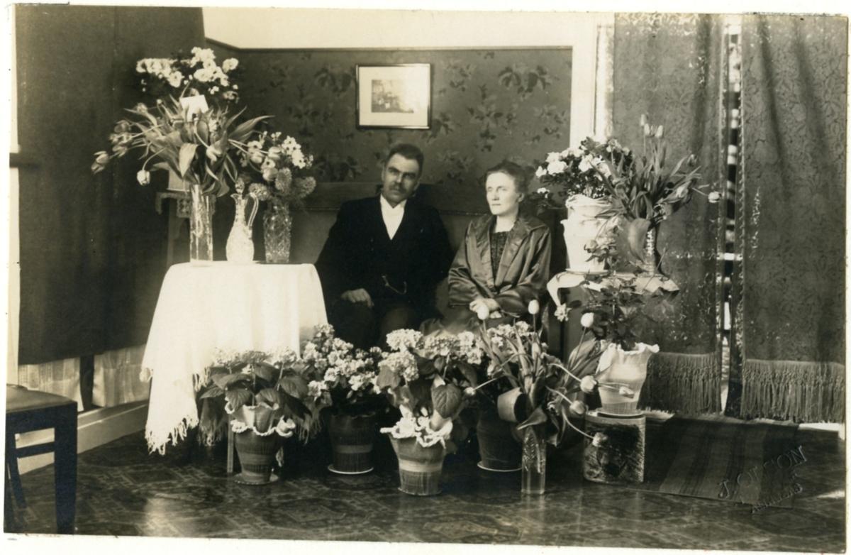 Typografen H.M. Enander och hans fru Anna fotograferade omgivna av blommor på silverbröllopsdagen 1924.