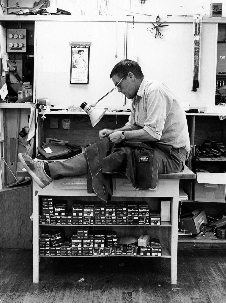 """Sven-Erik Joneskär, skräddare och verkmästare eller arbetande förman sitter på bordet och syr på en kavaj. Drabant AB. Kavajavdelningen, """"Kavajen"""", Drabant AB:s andra våning."""