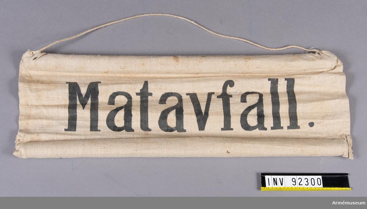 Skylt av tyg med träpinnar i sydda kanaler på långsidorna. Upphängningssnöre. Svart text: Matavfall.