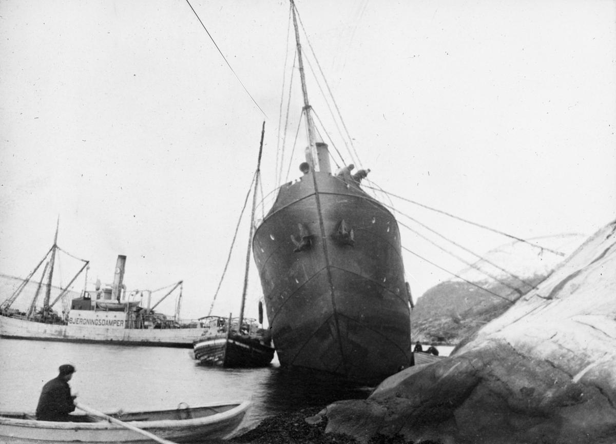 Arbeid i forbindelse med skipsbergning. Fartøyet har slagside og er fortøyd til land. Mann i robåt i forgrunn av motivet.