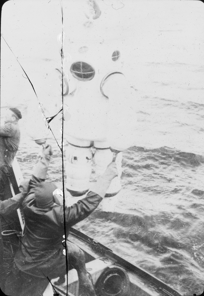 Dykker i panserdrakt heises ned i vannet fra båt.