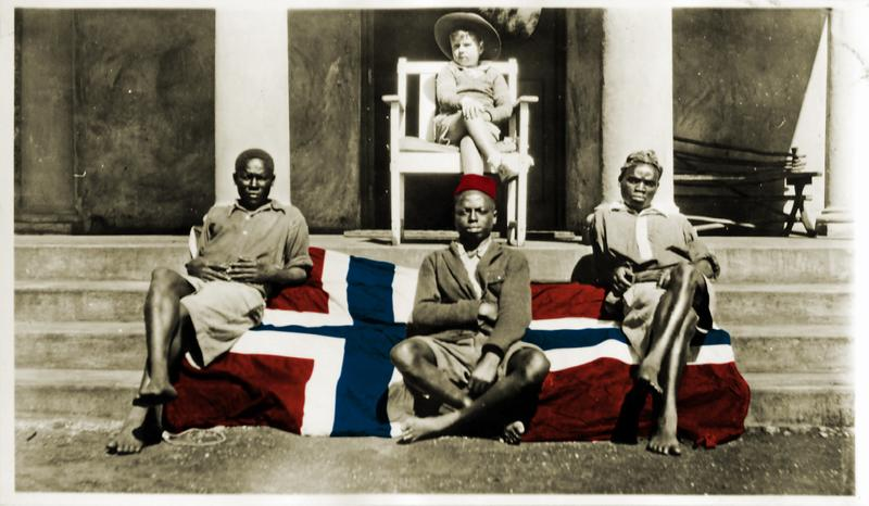 Kolorert bilde. Et norsk flagg er brettet ut over en trapp til en balkong, tre afrikanere sitter på flagget. En lys gutt sitter på en stol på balkongen.