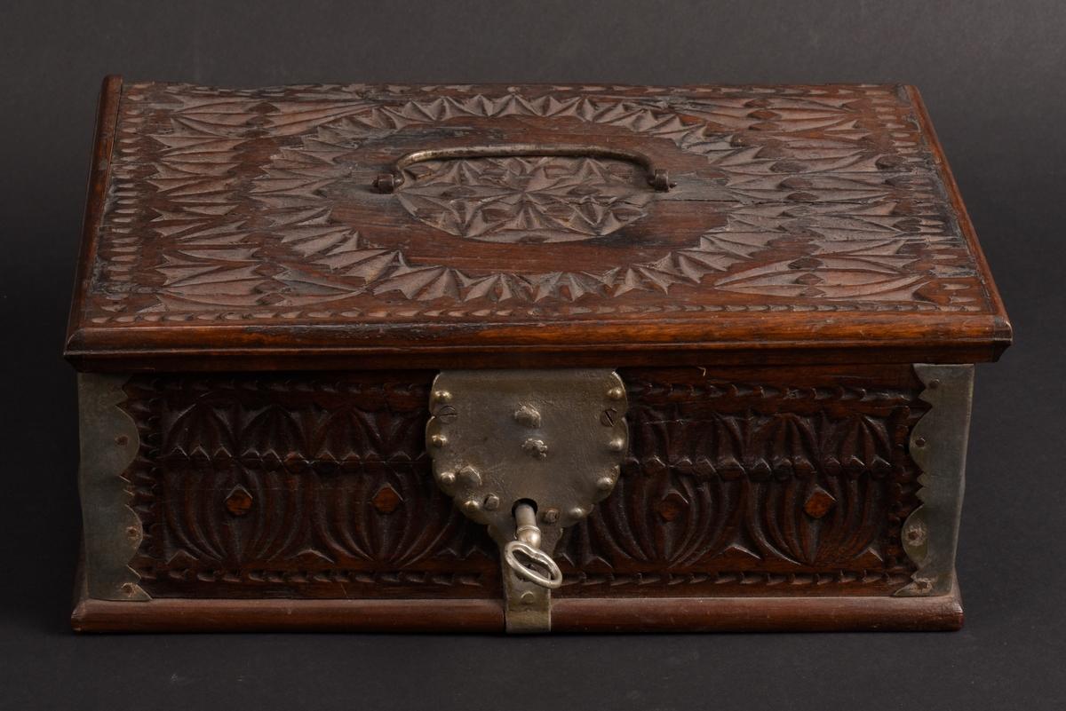 Rektangulärt skrin med plant lock av ek. Rikt dekorerad med karvsnitt bland annat i form av hjärtan. Utsirade hörnbeslag och ett handtag på locket av järn. På lockets insida påmålat årtal, 1759, samt initialerna KND. Beslag och nyckelskylt bemålade.