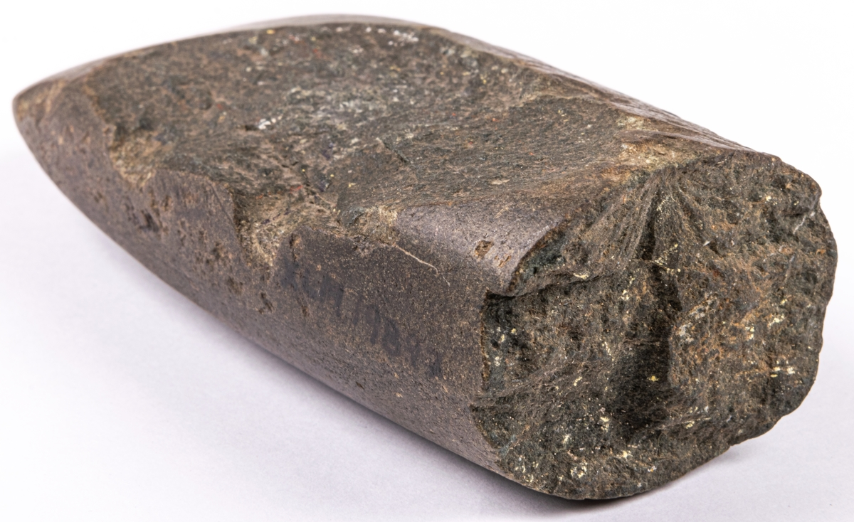 Yxa, av grönsten. Av typ kopierande tunnackig flintyxa. Datering: 2500-1500 f.Kr.