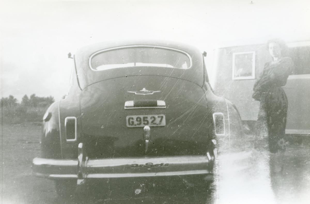 Framför en bostadsvagn står en bil parkerad. Mellan dem står en kvinna. Bland flera romska grupper har det historiskt varit vanligt att arbeta med hästar, som hästhandlare och valackare. Men under 1900-talet övergår bondesamhället i Sverige mer och mer i ett industrisamhälle och behovet av hästhandlare försvinner. Många svenska romer övergår nu till att bli bilhandlare, med stort intresse för och kunskap om bilar.