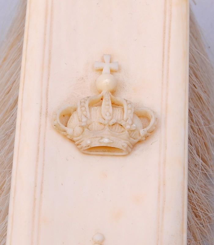 Gräddfärgad borste med handtag av elfenben och borst av animaliskt material, troligtvis gethår. Handtaget är format efter dess ornament som liknar akantusblad, mitt på handtaget finns pärlstavsdekor. Handtagets ornamentering fortsätter i relief en bit upp på borstens rygg. Ryggen är rektangulär och på mitten finns en kungakrona i relief.