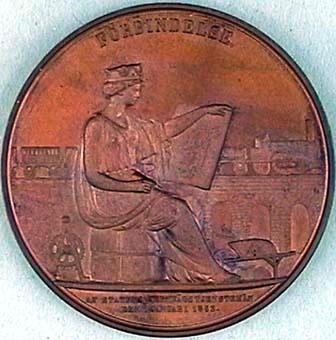 """Minnesmynt, minnesmedalj (:1) av koppar i etui (:2). Åtsidan har en bild föreställande ett mansansikte i profil. Mannen har vågigt hår och mustach. Runtom står det: """"NILS ERICSON CHEF FÖR STATENS JERNVÄGSBYGGNADER 1855-1862"""". Nedanför porträttet är den signerad """"LEA AHLBORN F."""" Frånsidan visar en sittande kvinna framställd som en antik gudinna med en draperad dräkt och en krona på huvudet. Kronan har tre bevingade hjul synliga i bilden. Kvinnan sitter på ett paket. I vänster hand håller kvinnan upp en karta av södra Sverige där hon har dragit järnvägslinjer. I bakgrunden syns ett ånglok med vagnar på en stenbro. På vänster sida om kvinnan står ett kugghjul som symbol för industrin. Till vänster om kvinnan står en skottkärra med redskap och en hög med stenar bredvid. Ovanför bilden är det graverat """"FÖRBINDELSE."""" Under bilden står det """"AF STATENS JERNVÄGSTJENSTEMÄN DEN 1 JANUARI 1863."""" Medaljen ligger i ett rött etui (:2) som är klätt med sammet invändigt."""