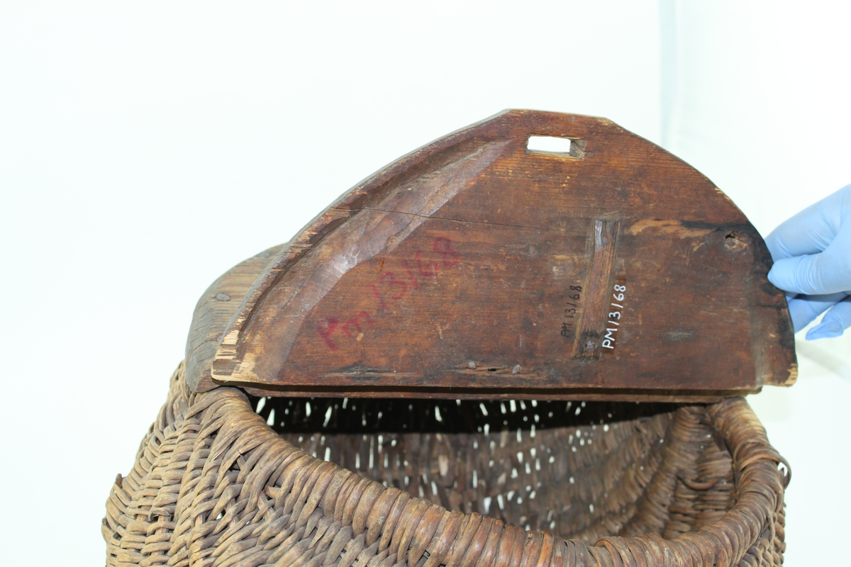 """Matsäckskorg, så kallad förselkorg (av forsla och förning = mat), bestående av flätverk med cirkelrunt lock av trä. Locket är delat på mitten och försett med gångjärn. Lockets ena hälft fastspikat i korgen. Andra hälften uppvikbar. Denna del kan tillslutas med ett rep, fäst i korgen och draget genom ett hål i lockets ena kant. Flätverket och gångjärnet söndriga. I nskuret i locket """"1860"""" och """"IuB9""""."""