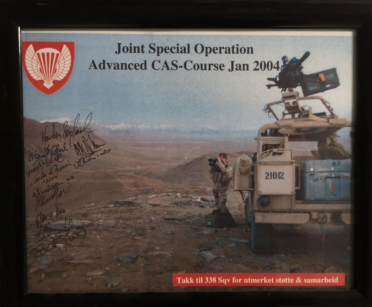 """Person med kikkert i ørkenterreng, med signaturer og pålimt text: """"Takk til 338 sqv for utmerket støtte & samrbeid."""""""