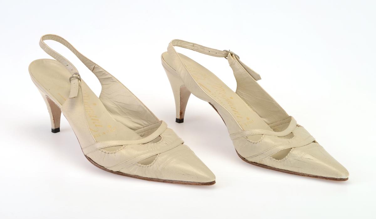 """Et par høyhælte skinnsko med stiletthæler til dame. Foran har de spiss tupp. På overlæret foran er det gjennomhullet mønster i form av halvsirkler på to """"rekker"""" (to i den ene rekken og tre i den andre rekken). Skoene er åpne bak, men det er en reim som går bak ankelen. Reimen festes i en liten sølvfarget metallspenne. Det er 7 hull for stramming på reimen. Innersålen er av lyst gråhvitt skinn. På sålen er det påført tekst i gull, se """"Påført tekst/merker"""". Skoen er foret med lyst gråhvitt skinn. Yttersålen er av brunt lær, men på hælen er det svart plast. Det er tekst på undersiden av skoene, se """"Påført tekst/merker""""."""