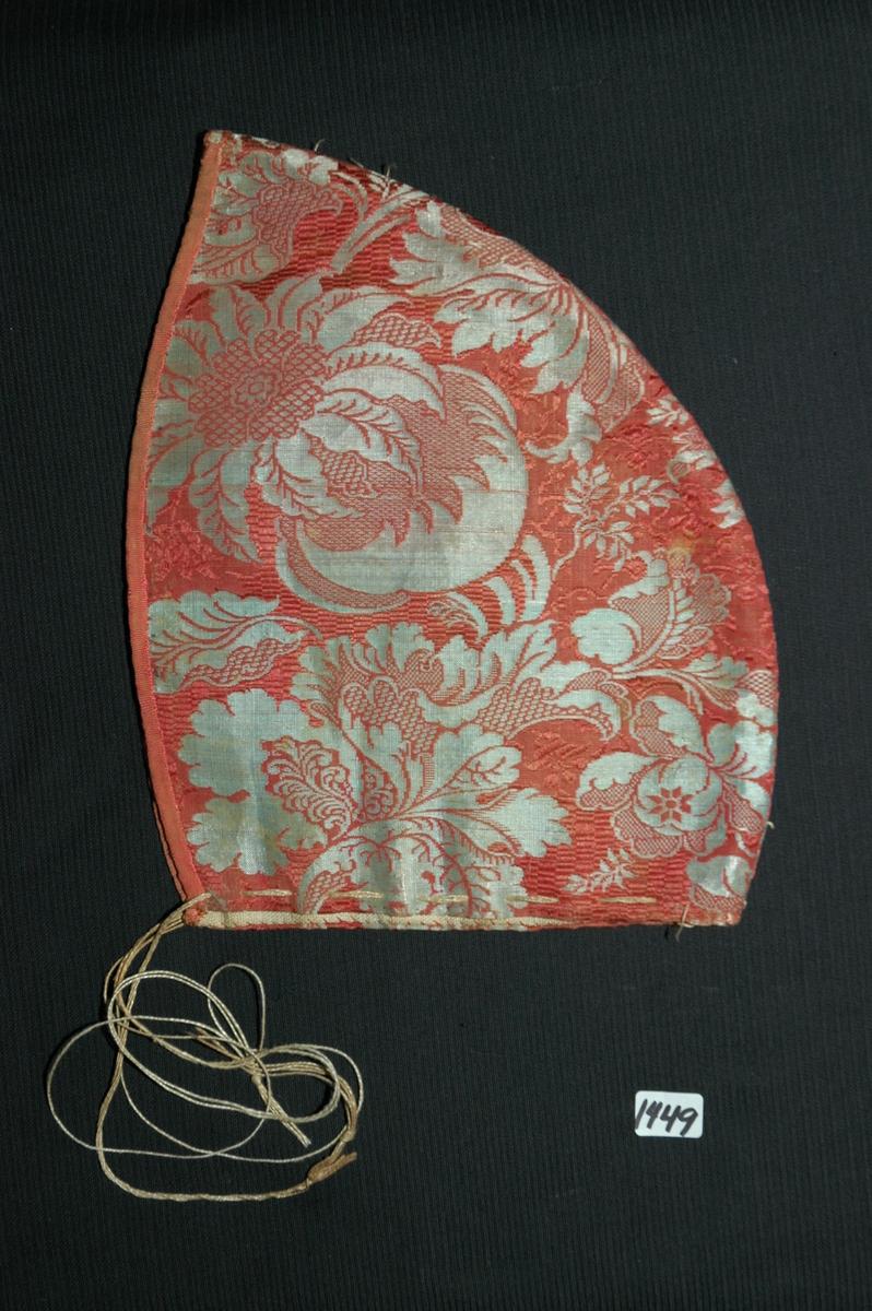 Lue, tobladlue av grått og rødt (lakserødt) silkestoff, akntet med rosa, ripsvevd damasklignende silke. Fôret er av linlerret, og lua er vattert med ukjent materiale. Sømmonnet er kastet over med lingarn med krssesting. Nedrekant er sydd ned med faldesting med silkegarn. Kantebandet er sydd fast med attersting og faldet med faldesting på vranga (0,5 cm). Trekksnor av lingarn. Rester av påfestet knipling? langs sammensyiningssømmen. Registrert av Bunad- og folkedraktrådet/Norsk institutt for bunad- og folkedrakt v/Jon Fredrik Skauge, 2005, revidert v/Bjørn Sverre Hol Haugen, 2020.