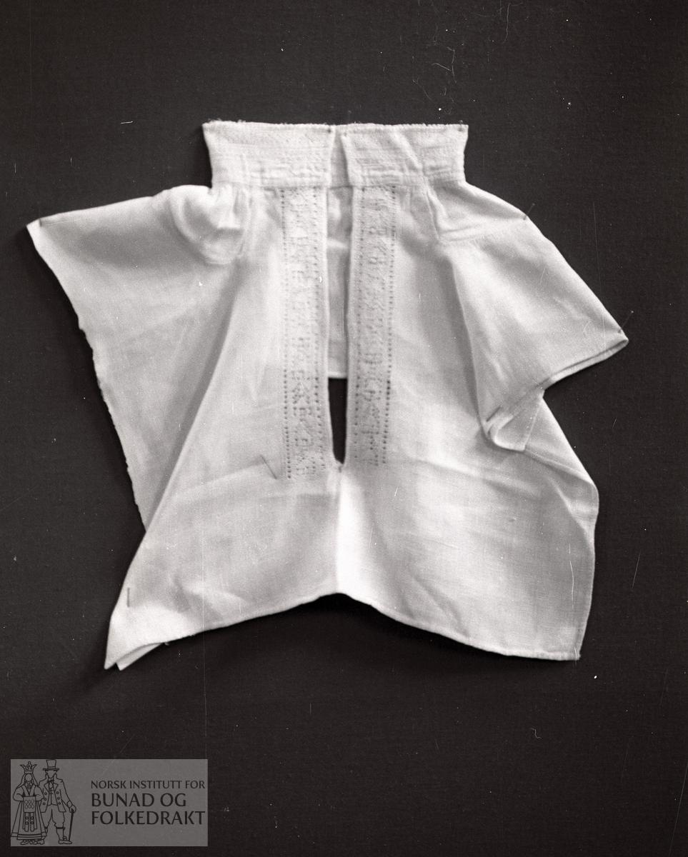Nordhordlandsmessa nr. 93.  -  Heimevoven lin.  Laga av eit stykke.  Lengde framme:  33 cm, breidde:  36 cm, lengde bak:  14 cm.  Firkanta kile på kvar skulder.  Rynkt til heile halslinninga, ein rynketråd.  Breidde halslinning:  4,0 cm, breidde bord halslinning:  2,5 cm, breidde bord langs splitten:  3,0 cm, lengde bord langs splitten:  19,5 cm.
