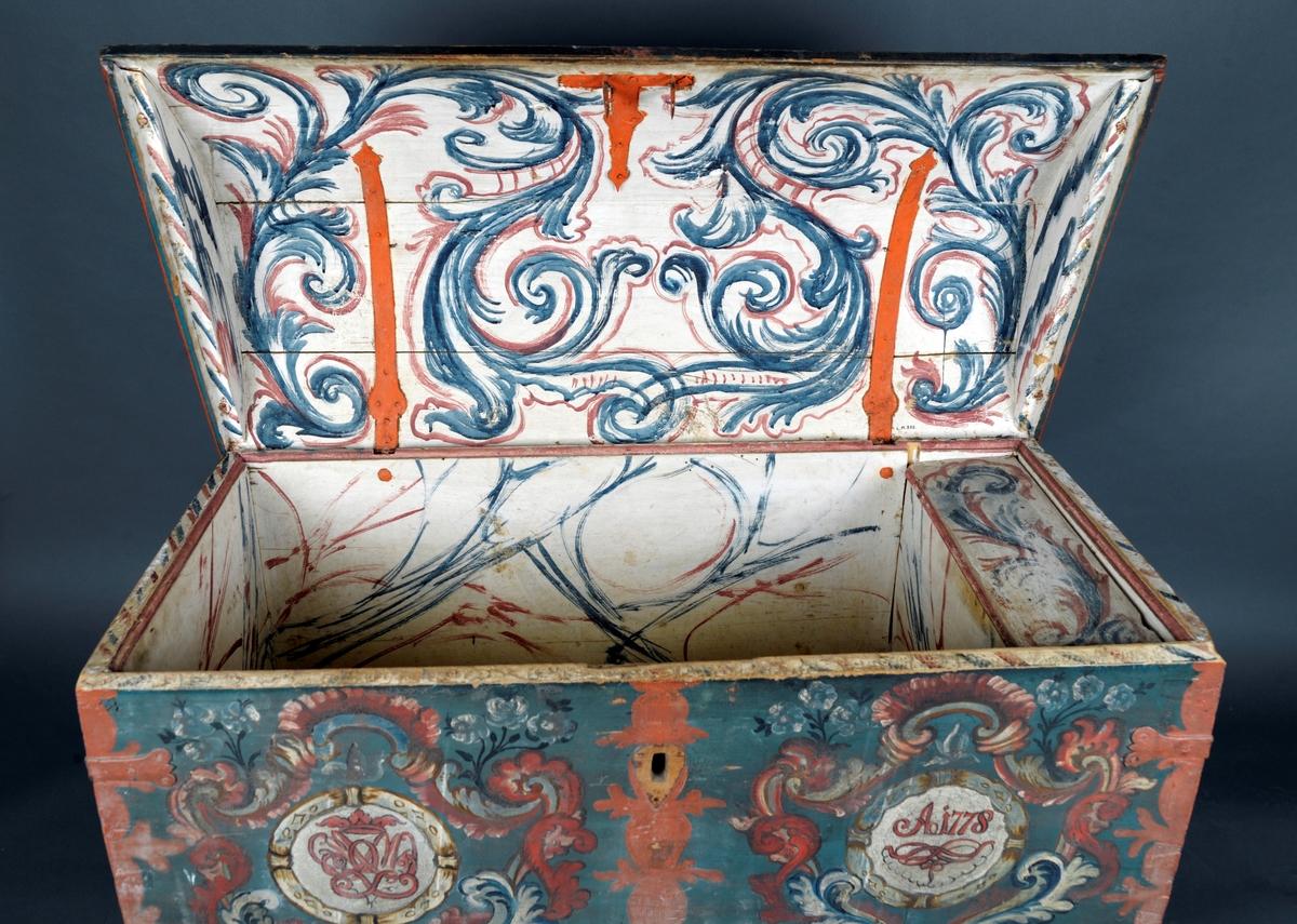 Rosemalt kiste, buet lokk, står på dreide ben.