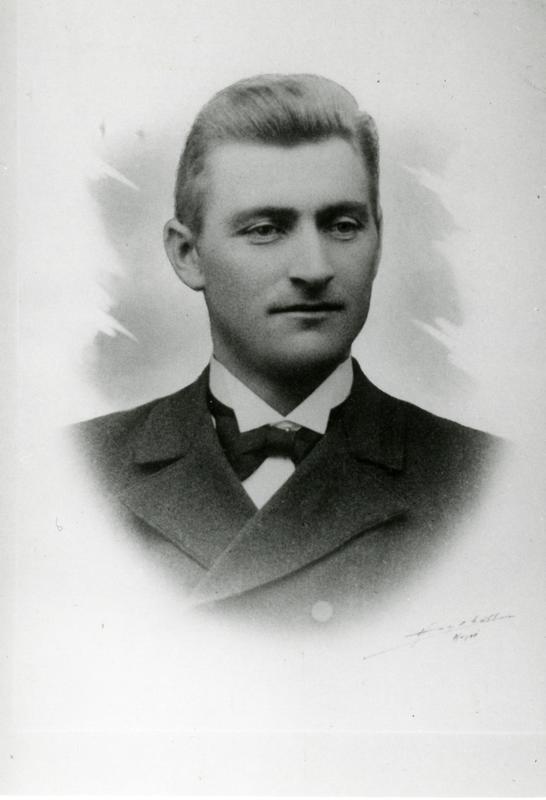 Portrett av en ganske ung mann med skjorte, sløyfe og jakke.