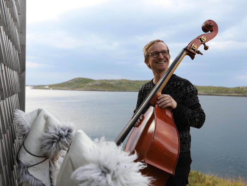 Sigurd Hole poserer med sin kontrabass utenfor en trehus ved vannet, lave fjell i bakgrunnen. (Foto/Photo)