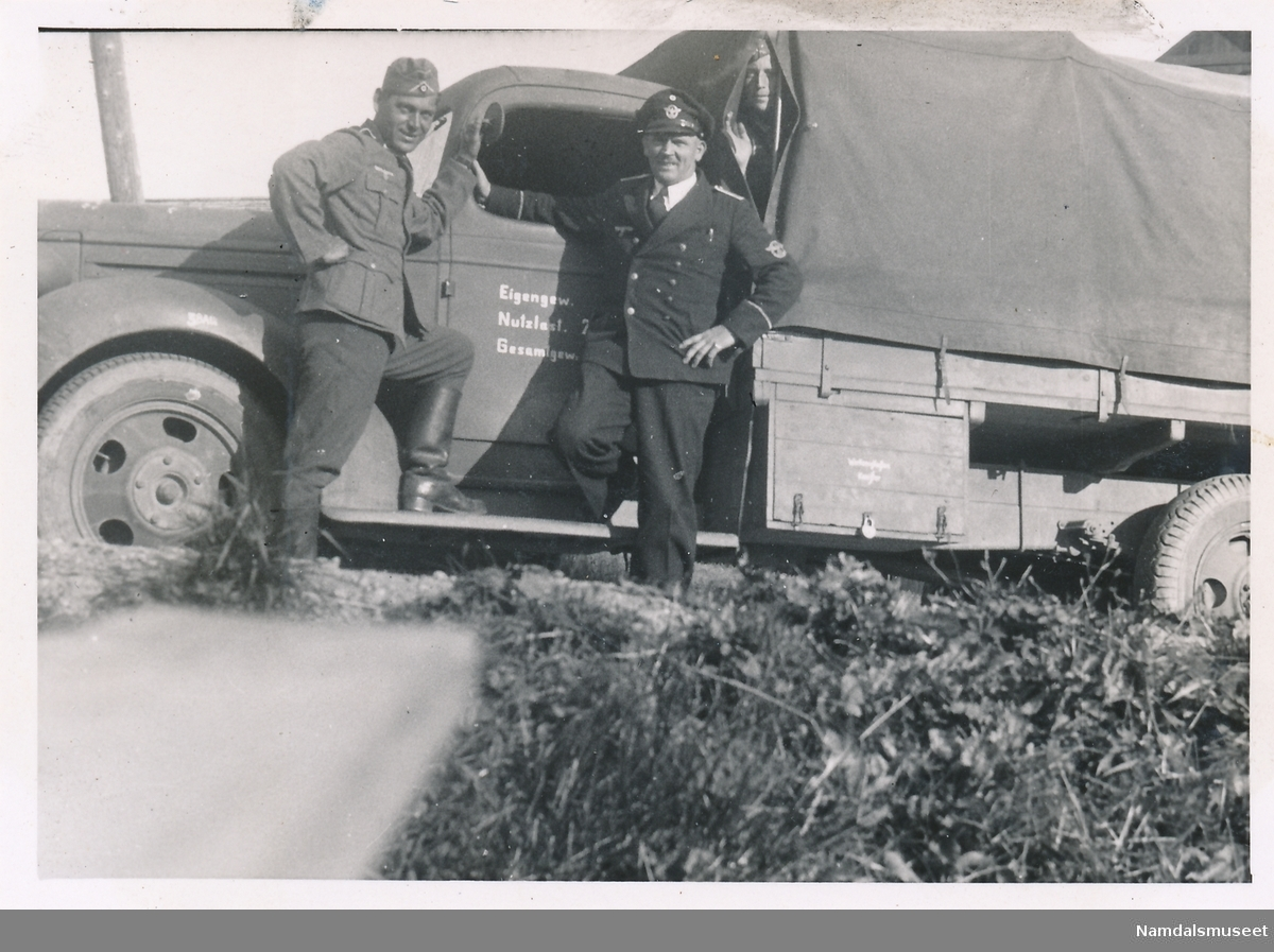 Tre tyske soldater ved tysk militærbil