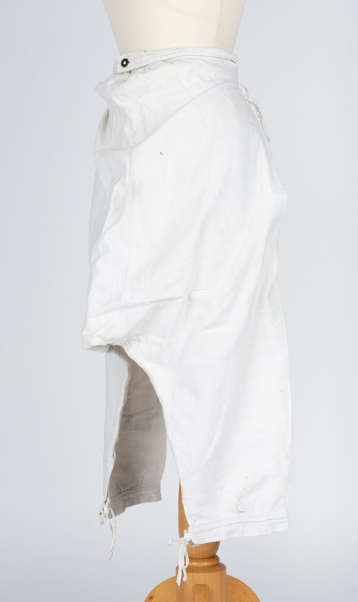 Knelange underbenklær. Lang splitt i beffe sider. Bakstykket sydd av 3 bredder, fasongkiler øverst mot linningen. Bakstykkets linning har bendelbånd som kan knyttes forran.  Forstykket sydd av 2 stykke, lange kiler fra skrittet til linningen. Den forlengede linningen på forstykket kneppes midt bak. Store lapper på begge forstykker. Stopping på begge kilene i skrittet . Slitasjehull øverst på forstykket og på linningen. Bukseben har splitt , linning og knyttebånd.  Gitt av Åse Huseby, Oppegård, Frogn. Formidler Greta Christiansen. Brukt av søstrene Christiansen, på Brevik