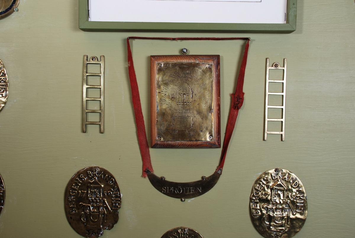Tavle med påmontert brannskilt fra Borgervæpningens tid. De enkelte tegnene er montert på platen med skruer. Tavlen har ramme rundt og flettet snor som dekorasjon limt på i overgangen mellom plate pg ramme.