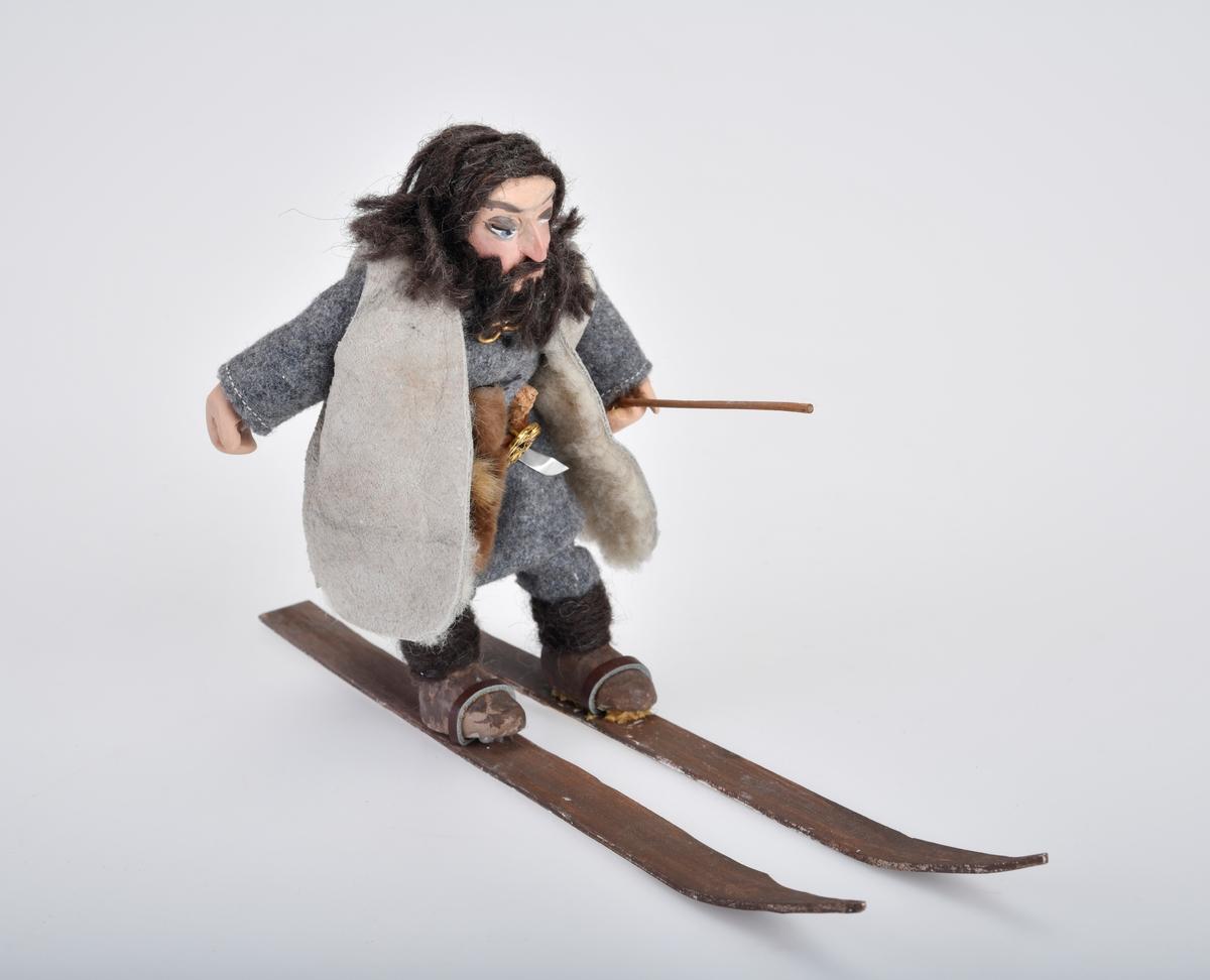 Liten mannsfigur med ski på beina og en skistav/langstav i hånden.