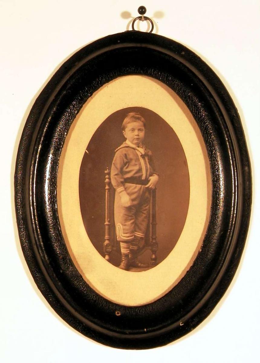 Fotografi av gutt stående på stolsete, kledd i matros drakt med bredt mørkt belte om livet, stripete strømper og støvler. Han ser direkte på betrakteren.