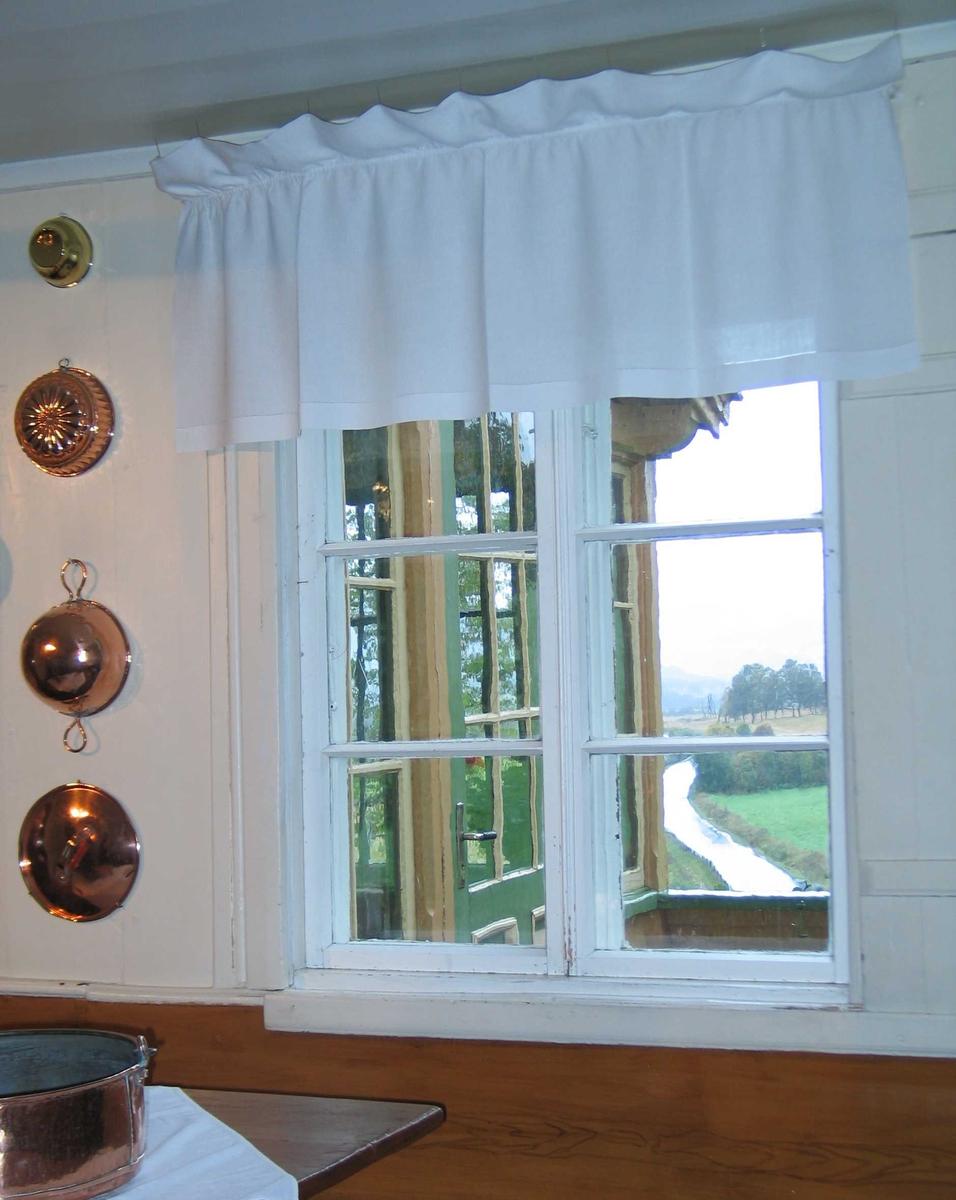 Gardin i hvit lin med stikkhullfall. Jare i sidene. 14 cm brett med 1,3 cm løpegang for opphenging. Rynkehodet blir ca 12,5 cm høyt.