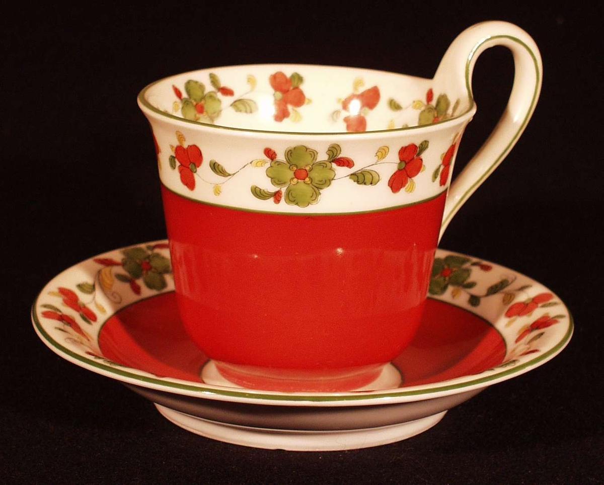 Prot.: Brun-rød dekor, overkant og innvendig gullig, blomster langs koppens utvendige og innvendige overkant, lignende rosemønster. Øverst grønn stuk som også følger hanken.