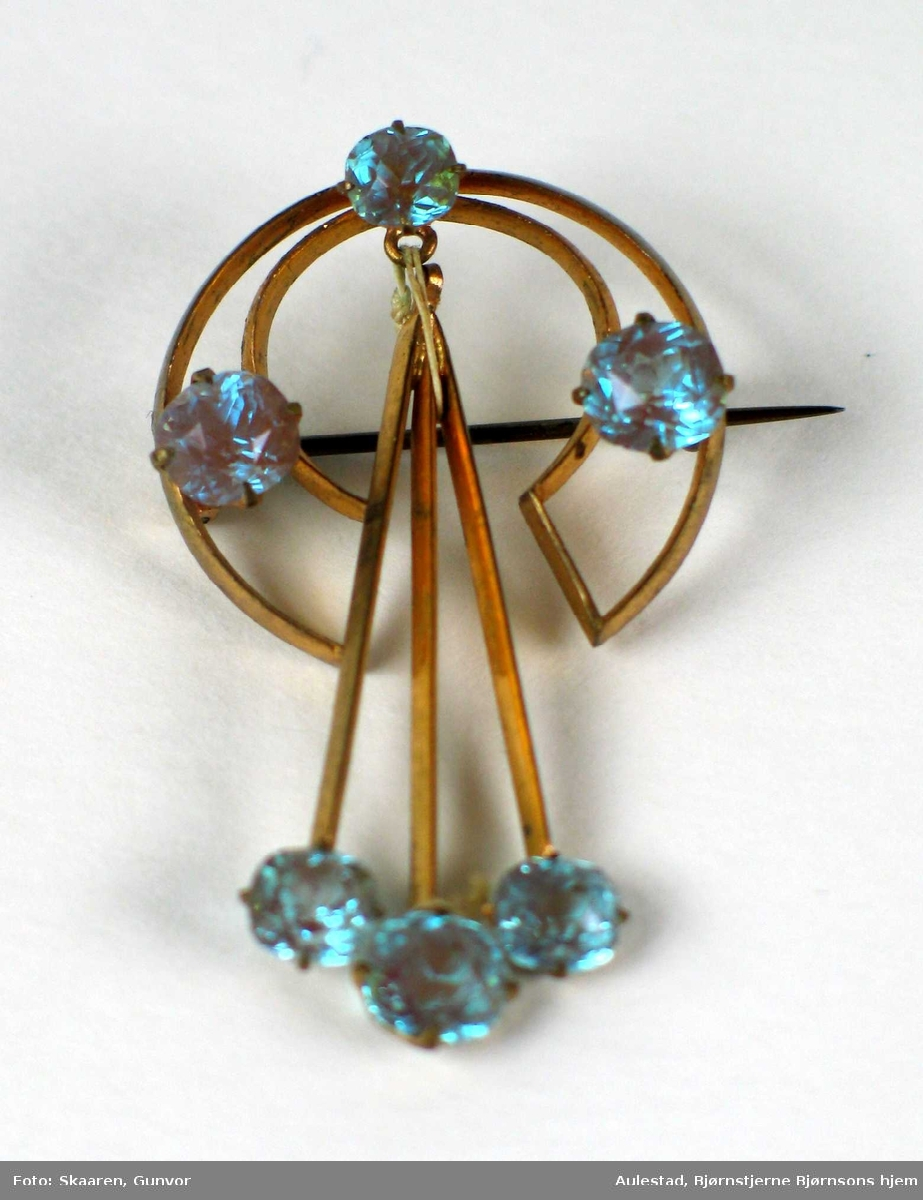 C-formet forgylt nål med tre hengende stenger og seks slipte turkise steiner.