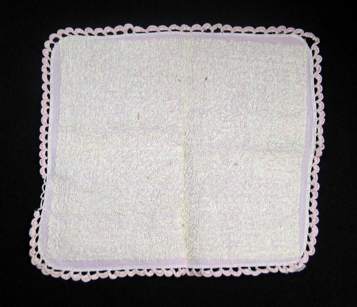Rosa vaskeklut i bomullsfrotté. Den er lik på begge sider og er maskinoverkastet på alle sider. Kluten har en heklet åpen tungekant av rosa bomullsgarn som danner hempe i det ene hjørnet, ikke fullført.