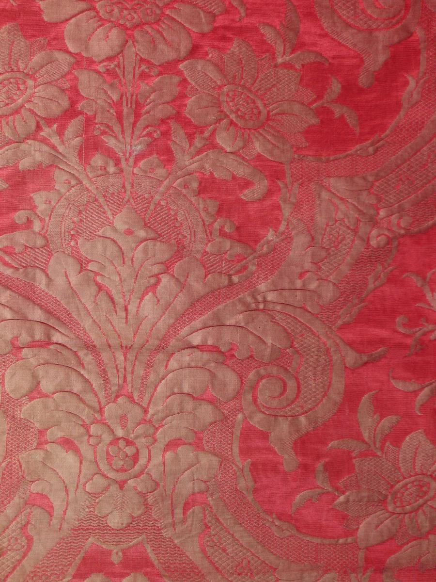 Rødt mønstervevd sengeteppe i silke med rødt fôr i bomullssateng.