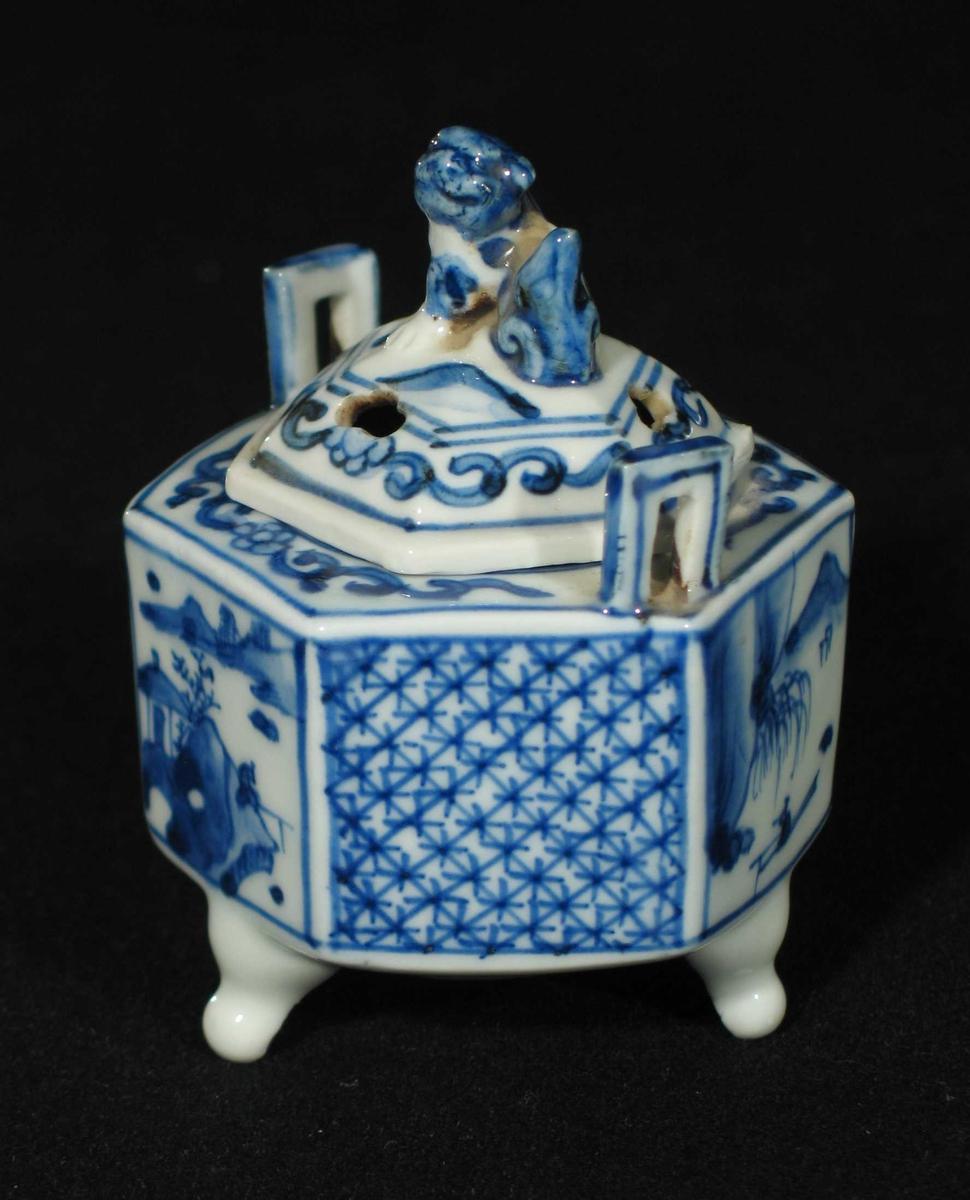 Røkelseskar i porselen med tre små bein, hvit underglasur og blå overglasur. Karet er sekskantet med to håndtak. Felter dekorert med landskap og kryssmønster. Hundefigur på toppen.