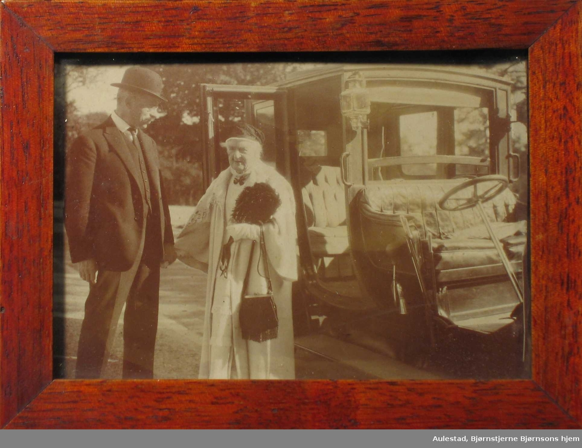 Mann og eldre kvinne står ved en landauer.