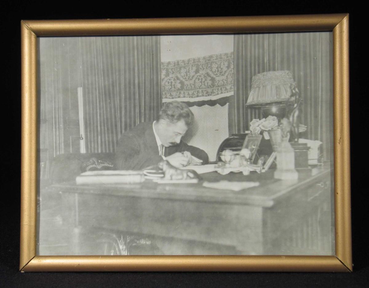Mann sittende ved et skrivebord.