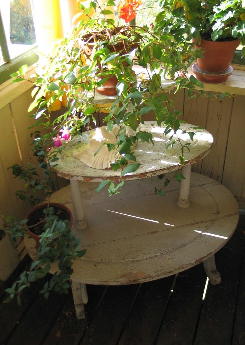 Hvitmalt blomsterbord i tre etasjer. Hyllene er ovale og holdes oppe av dreide profilerte staver. Møbelet har buede, skårne bein.