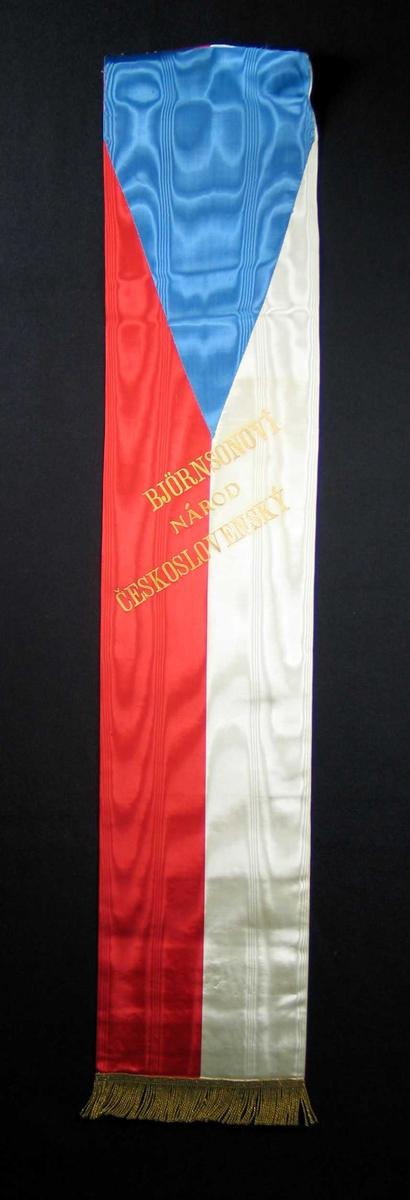 Silkesløyfe i rødt, hvitt og lyseblått med gullfrynser.