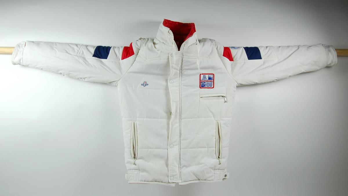 a1454639 Hvit, rød og blå vinterjakke. Det er en liten hette på jakka som kan