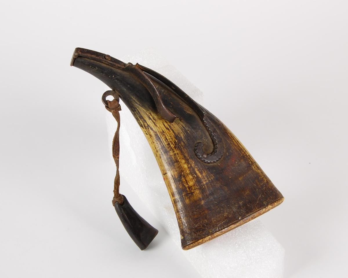 Ovalt krutthorn med fjærbelastet jernlås. Bunnplate av tre. Jernøye for oppheng med lærreim og påhengt kruttmål av horn.