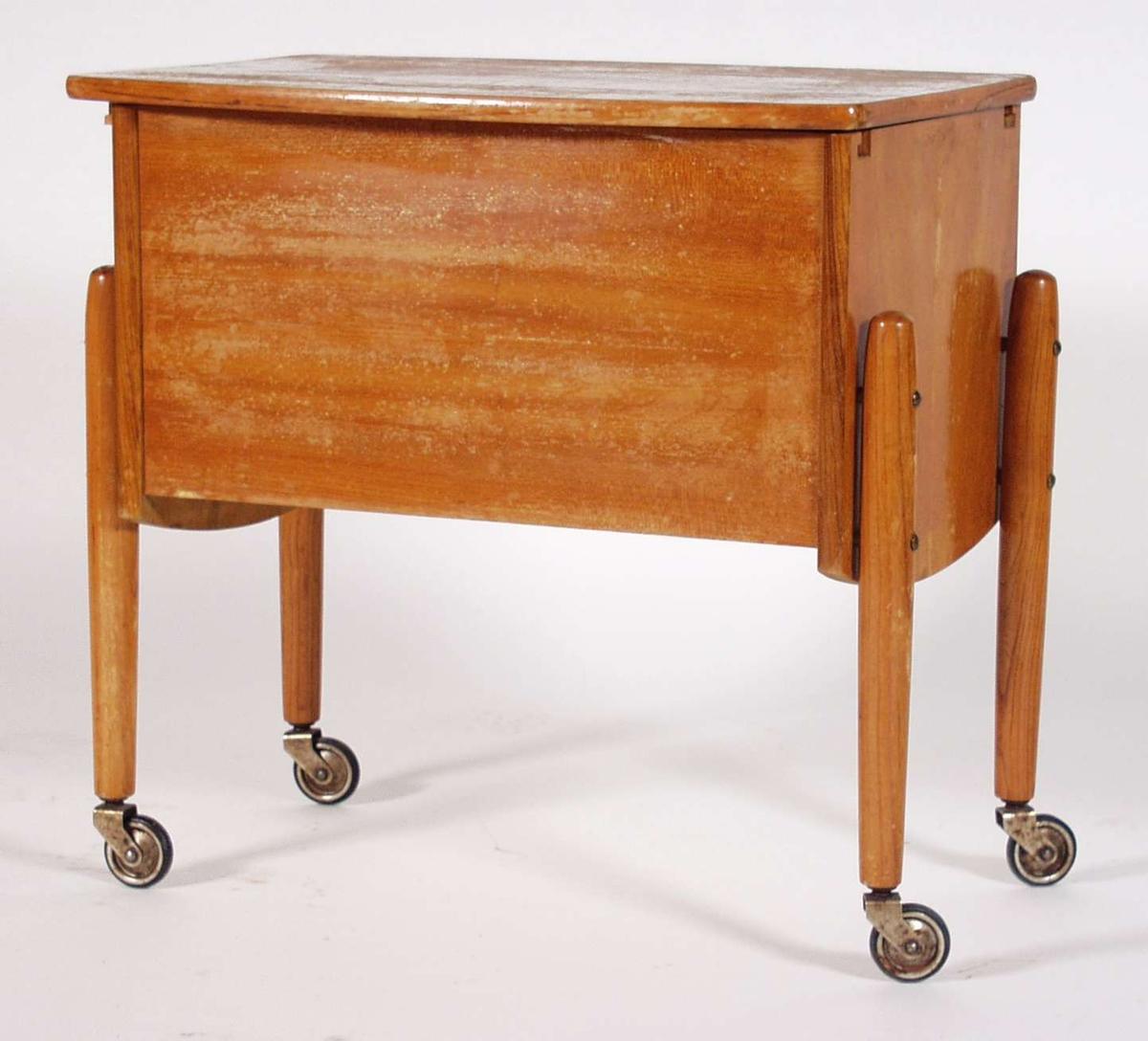 Et sybord i bjørk og eikefinér. Bordplaten erskyvbar til begge sider og en skillevegg tvers over på midten i sargen. Bena er påskrudde med hjul. Bordet er lakkert.