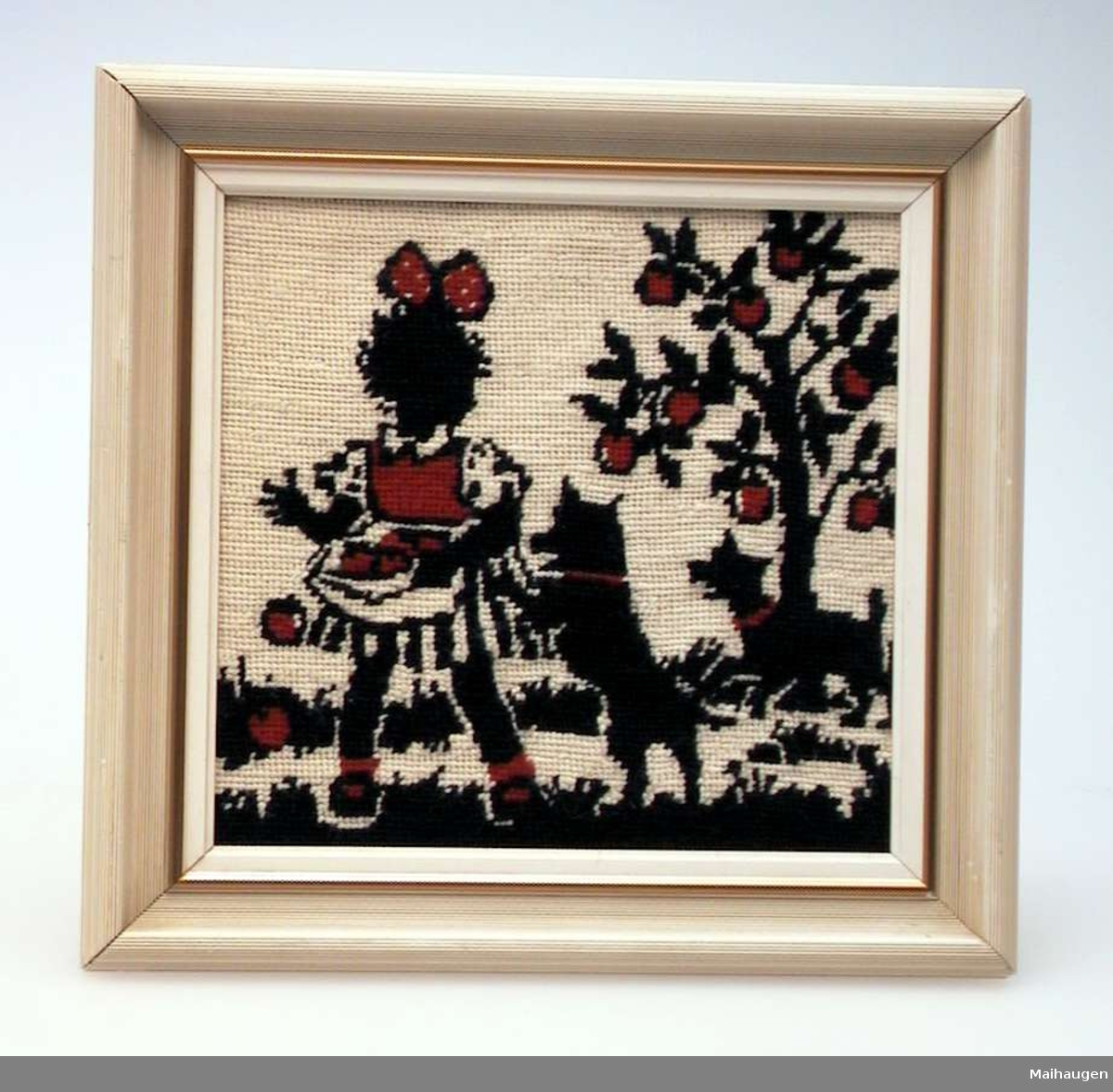 Ullbroderi på stramei i rødt, svart og hvitt. Motivet er ei jente med to hunder og et epletre i bakgrunnen. Rammen er av tre, malt hvit med gullkant.