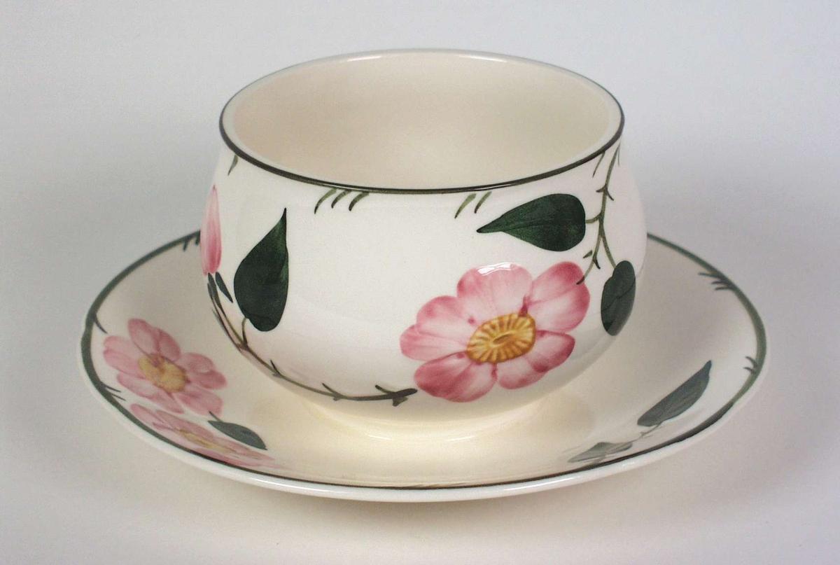 Kopp festet på skål dekorert med rosa nyperoser og grønne blad. Det er struktur i godset der det er malt.