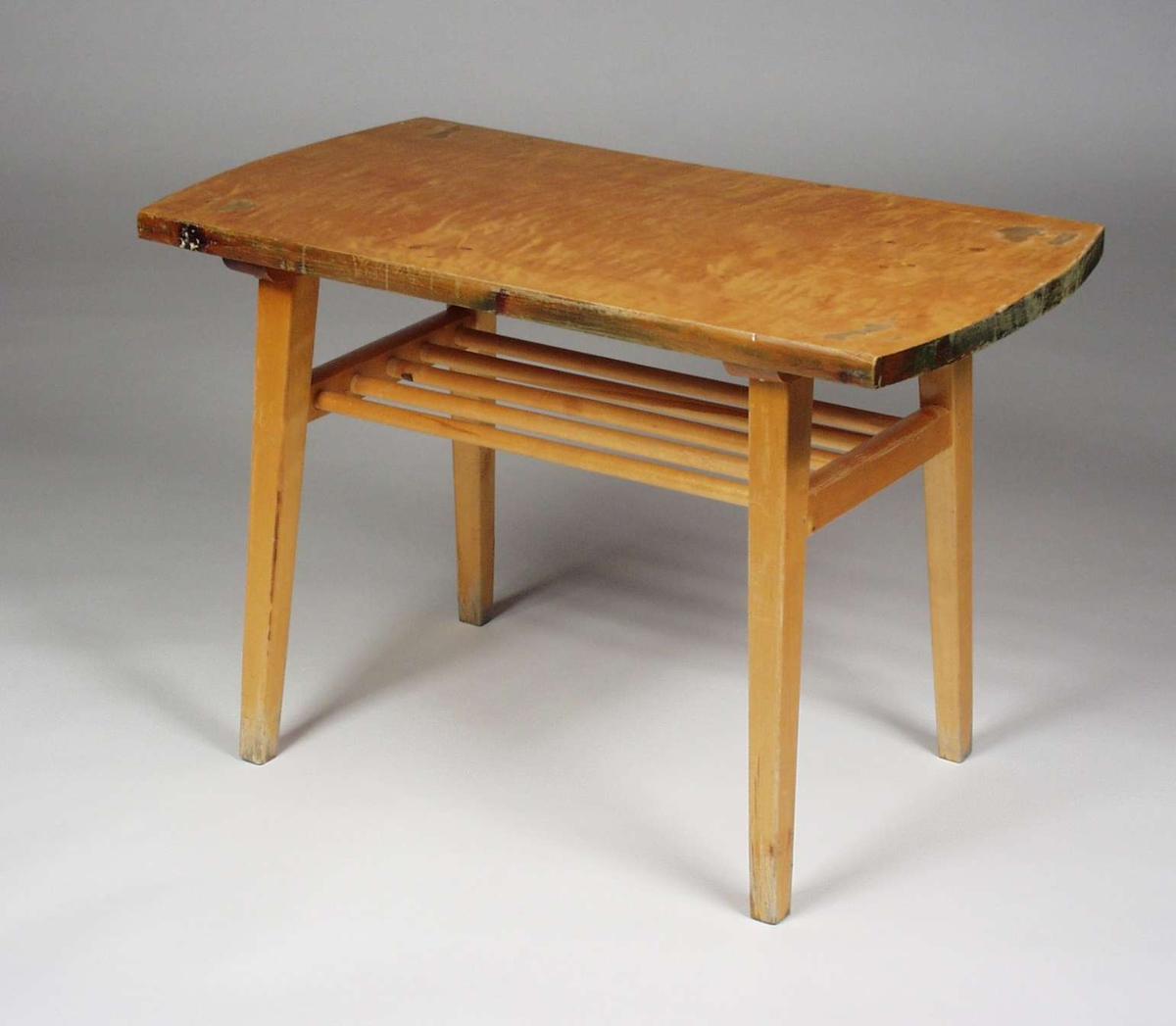 Et lakkert bord i furu og bjørk. Det har en hylle med sprinkler og bordplaten er finért.