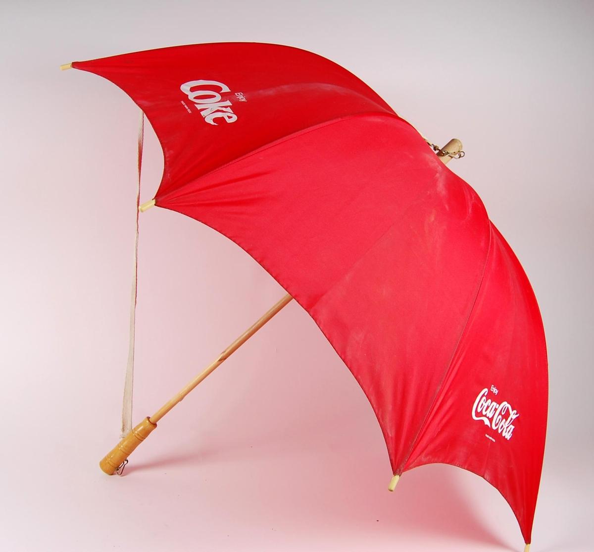 Rød paraply av nykonstoff og trestang inni. Paraplyen har avtagbar bærestropp av et hvitt vevd bomullsbånd. . Coca Cola-reklame i hvitt trykt på paraplyen. Hvert motiv er trykt to ganger.
