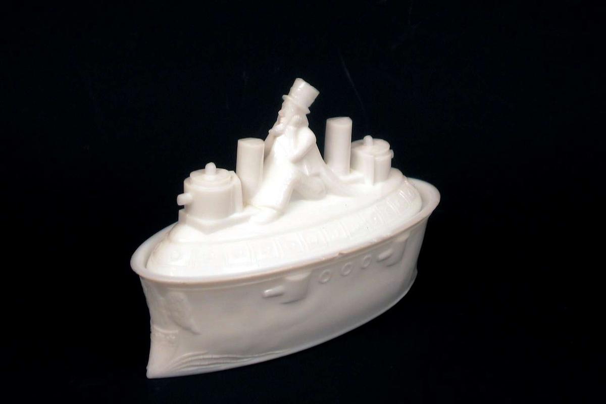 Skål med lokk i hvitt glass. Skålen med lokk er formet som et skip. På lokket sitter John Brown.
